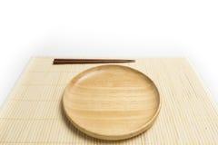 La placa o la bandeja de madera con los palillos coloca una estera de bambú aislada en el fondo blanco Fotos de archivo