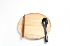 La placa o la bandeja de madera con los palillos y la cuchara aisló el fondo blanco Imagenes de archivo