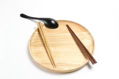La placa o la bandeja de madera con los palillos y la cuchara aisló el fondo blanco Foto de archivo libre de regalías