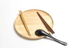 La placa o la bandeja de madera con los palillos y la cuchara aisló el fondo blanco Fotos de archivo