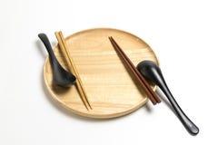 La placa o la bandeja de madera con los palillos y la cuchara aisló el fondo blanco Fotografía de archivo libre de regalías