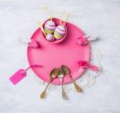 La placa rosada de Pascua con las cucharas, los huevos y la tabla firman Fotos de archivo libres de regalías
