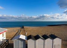 La plage baignant des maisons échouent les cabines/huttes changeantes de plage, la plage rocheuse et la mer contre le ciel bleu e photos libres de droits