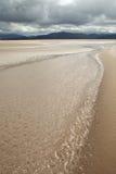 la plage de sable de l'eau opacifie le fond foncé de ciel Images stock