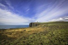 La plage noire de sable avec le phare sur la falaise, Islande Photos stock