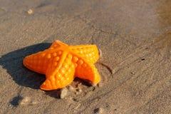 La plage ondule des étoiles de mer et des jouets colorés Photo stock