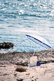 La plage pierreuse avec le parasol image stock