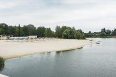 La plage près de la rivière avec des canapés du soleil Photo libre de droits