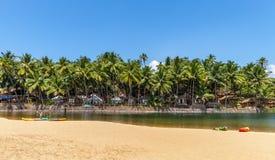 La plage sablonneuse avec le canoë et les jeunes le long de la bouche de t Photo libre de droits