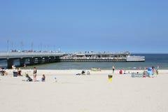 La plage sablonneuse et le pilier dans Kolobrzeg Image stock