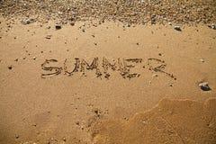 La plage sablonneuse ondule à l'inscription d'été de mer de coucher du soleil sur le sable Photos stock