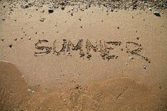 La plage sablonneuse ondule à l'inscription d'été de mer de coucher du soleil sur le sable Photo stock
