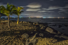 La plage tropicale la nuit avec la ville s'allume à l'arrière-plan - HDR Images stock