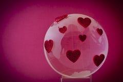 La planète de l'amour. Globe en verre avec les coeurs rouges. Images stock