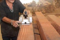 La planeuse électrique est travaillée avec des mains de charpentier supérieur dans l'atelier de menuiserie Centre sélectif et pro Photos libres de droits