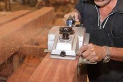 La planeuse électrique est travaillée avec des mains de charpentier supérieur dans l'atelier de menuiserie Centre sélectif et pro Photo libre de droits