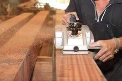 La planeuse électrique est travaillée avec des mains de charpentier supérieur dans l'atelier de menuiserie Centre sélectif et pro Image stock
