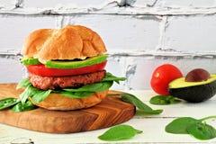 La planta basó la hamburguesa meatless con el aguacate, el tomate y la espinaca contra un fondo blanco del ladrillo fotografía de archivo libre de regalías