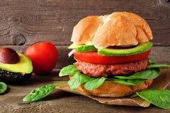 La planta basó la hamburguesa meatless con el aguacate, el tomate y la espinaca contra un fondo de madera imagen de archivo