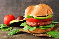La planta basó la hamburguesa meatless con el aguacate, el tomate y la espinaca contra un fondo oscuro fotos de archivo