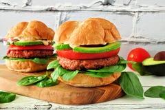 La planta basó las hamburguesas meatless con el aguacate, el tomate y la espinaca contra un fondo blanco del ladrillo foto de archivo libre de regalías