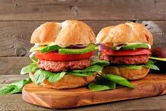 La planta basó las hamburguesas meatless con el aguacate, el tomate y la espinaca contra un fondo de madera imagen de archivo libre de regalías