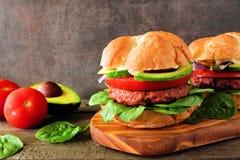 La planta basó las hamburguesas meatless con el aguacate, el tomate y la espinaca contra un fondo oscuro imagen de archivo