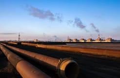 La planta enorme en el fondo de la mentira instala tubos en la puesta del sol Imagenes de archivo