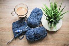 La planta verde en el pote, las agujas que hacen punto, el hilado azul, y el café sólo están en la tabla fotos de archivo