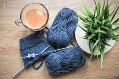 La plante verte dans le pot, les aiguilles de tricotage, le fil bleu, et le café noir sont sur la table Photo libre de droits