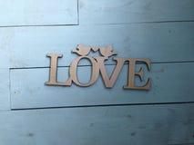 La plaque a découpé en bois avec un amour d'inscription sur un fond bleu Photo stock