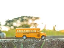 la plastica ed il metallo dello scuolabus giocano il modello sul paese roa Fotografie Stock Libere da Diritti