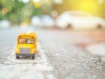 la plastica ed il metallo dello scuolabus giocano il modello sul paese roa Immagini Stock Libere da Diritti