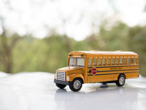 La plastica ed il metallo gialli dello scuolabus giocano il modello sul paese roa Fotografia Stock