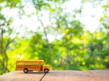 La plastica ed il metallo gialli dello scuolabus giocano il modello sul paese roa Fotografie Stock