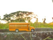 La plastica ed il metallo gialli dello scuolabus giocano il modello sul paese roa Fotografie Stock Libere da Diritti