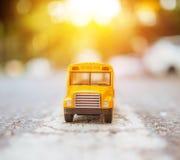 La plastica ed il metallo gialli dello scuolabus giocano il modello sul paese roa Fotografia Stock Libera da Diritti