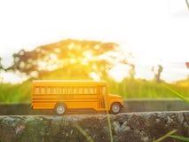 La plastica ed il metallo gialli dello scuolabus giocano il modello sul paese roa Immagine Stock