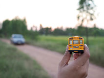 La plastica ed il metallo gialli dello scuolabus giocano il modello sul ro del paese Fotografia Stock
