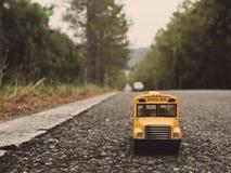 La plastica ed il metallo gialli dello scuolabus giocano il modello sul paese roa Immagini Stock Libere da Diritti
