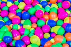 La plastica variopinta eggs i giocattoli che galleggiano sull'acqua Fotografia Stock