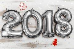 La plata metalizada brillante hincha los cuadros 2018, la Navidad, globo del Año Nuevo con las estrellas del brillo en la tabla d Fotografía de archivo