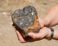 La plata remonta en la roca en su mano foto de archivo libre de regalías