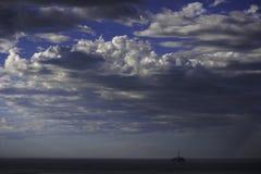 La plate-forme de forage de pétrole solitaire sous le ciel nuageux comme tempête s'approche images libres de droits