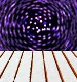 La plate-forme en bois avec la neige et la tache floue de mouvement allume le fond Image stock