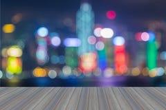 La plate-forme en bois avec le résumé a brouillé le skylin de lumières de ville de Hong Kong de bokeh Photo stock