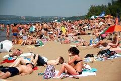 La playa apretada del verano, gente toma el sol en el sol foto de archivo