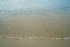 La playa arenosa limpia en colores pastel suave con la agua de mar clara fresca y la onda espumosa blanca alinean el fondo y el c Imagenes de archivo