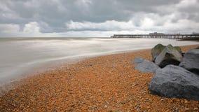 La playa colorida de Hastings con el embarcadero reconstruido en 2016 en el fondo y un cielo nublado, Hastings, Reino Unido Imagenes de archivo