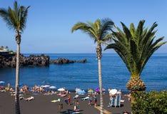 La playa con la arena y los turistas volcánicos negros Imagenes de archivo